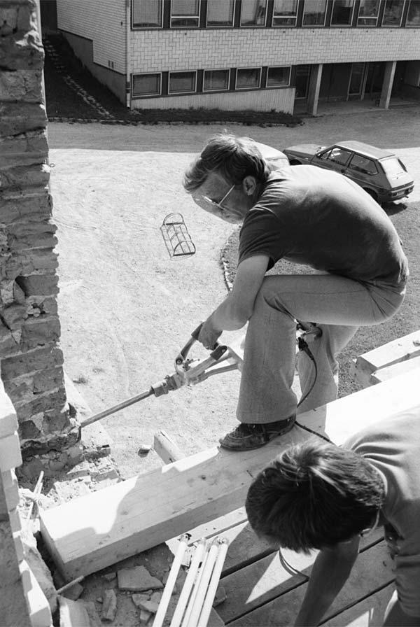 """Erik Kronlund öppnar väggen från kursgårdens """"tjänarinnetrappa"""" för att kunna bygga en övergång till nya skolhuset."""