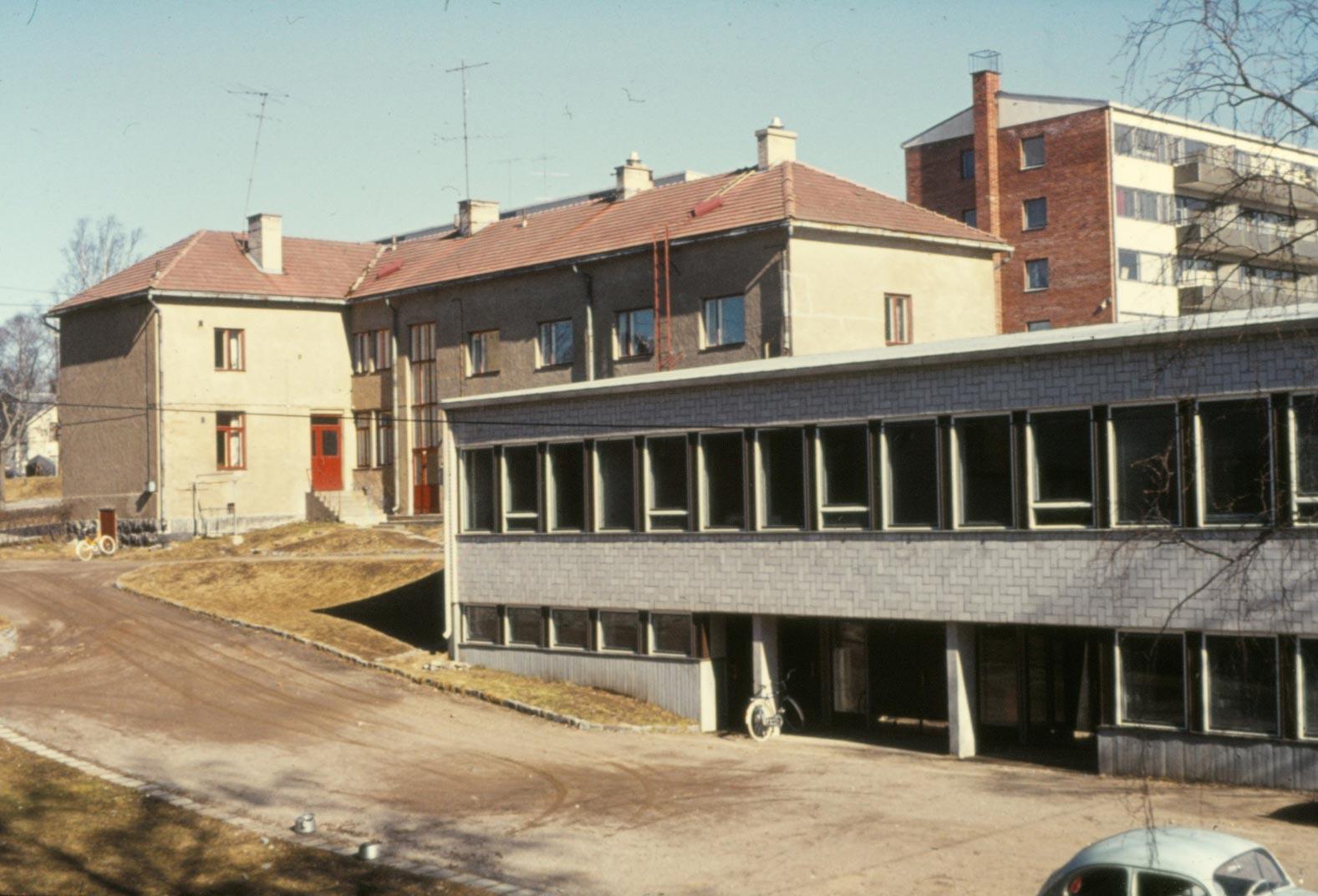 Det gamla huset med personalbostäder och pojkinternat uppe i backen och nedanför verkstadsbyggnaden från 1963.