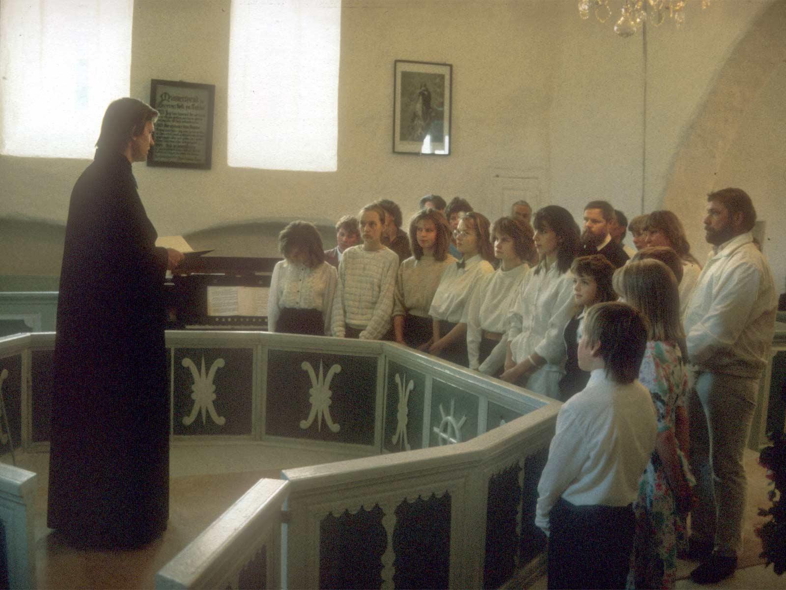 Leevi Reinaru talar till en grupp ungdomar och deras faddrar som blir döpta i Lääne-Nigula kyrka 3.6.1990.